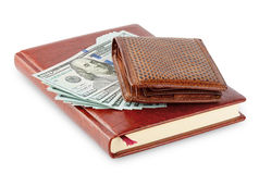 Diary and brown leather wallet with a wad of hundred dollar bill. S isolated on white background Stock Photo