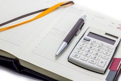Diary with calculator and pen on white background, business manager set. royalty free stock photography