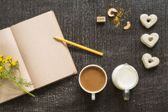 Diary with coffee, flowers and cookies on black Stock Photography