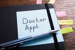 Diary Of Doctor Appointment On Desk. High Angle View Of A Diary Of Doctor Appointment With Sticky Note On Desk Royalty Free Stock Image