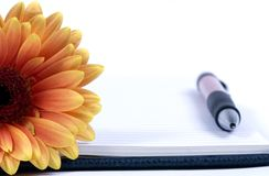 Diary and flower. A personal daily diary with a single orange flower. Ready for todays entry Stock Photo