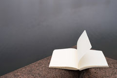 Diary with a flying page on riverbank Royalty Free Stock Photo