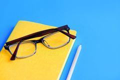 diary on it are glasses next to a pencil on a blue background stock image