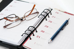 Diary with glasses and pen Stock Image