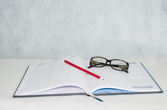 Diary, glasses and a pencil Stock Photos