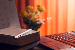 Diary and labtop for work on wooden table with flower and red curtain,notebook,book,pen,diary,clock and on wooden desk,Working. Space at home background office stock image