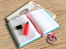 Diary losing weight women. Diary of a woman losing weight, scale and measuring tape lying on the mat Stock Photos