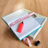 Diary losing weight women. Diary of a woman losing weight, scale and measuring tape lying on the laminate floor Stock Photography