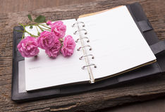 Diary note with pink rose on old wood Royalty Free Stock Photography
