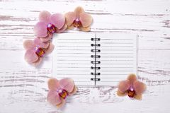 Diary on old wooden table decorated with orchid flowers Stock Photos