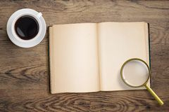 Diary or open book with loupe and coffee cup. On wooden table Royalty Free Stock Image