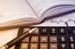 Diary pen and calculator. Over annual report Stock Photos