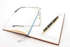 Diary, pen and glasses. Open diary with page marker,  pen and spectacles isolated on a white background Stock Images