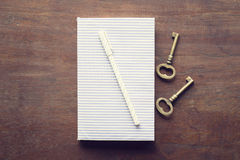 Diary with pen and keys on a wooden table Royalty Free Stock Image