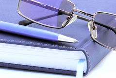 Diary, pen and reading glasses over white. Background Stock Photos