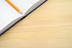 Diary and pencil on wooden table. Open a blank white notebook on the desk with free text space. Royalty Free Stock Image