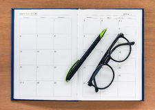 Diary planner book open calendar page with glasses and pen on th Royalty Free Stock Photography