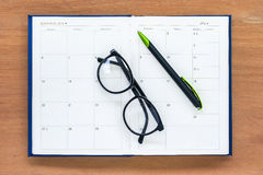 Diary planner book open july calendar page with glasses and pen on th Royalty Free Stock Photo