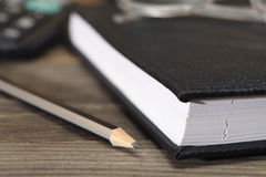 The diary and a simple black pencil lie on the desktop. Close-up. Selective focus. Royalty Free Stock Photos