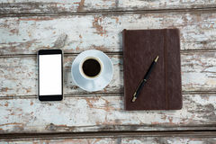 Diary, smartphone and pen with coffee cup. On table Stock Photos