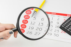 Dias de calendário que olham através da lupa imagem de stock