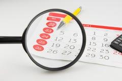 Dias de calendário que olham através da lupa imagens de stock