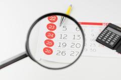 Dias de calendário que olham através da lupa foto de stock