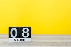 Dias internacionais felizes do ` s das mulheres 8 de março Dia 8 do mês, calendário na tabela com fundo amarelo Espaço vazio para Fotos de Stock
