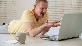 Dibattito insoddisfatto dell'uomo delle free lance ai colleghi in una video chiacchierata su un computer portatile sul pavimento stock footage