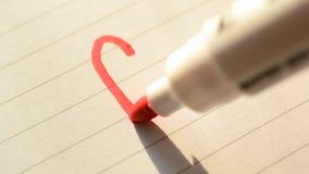 Dibujando un corazón forme con una pluma de extremidad de fieltro roja en el papel metrajes