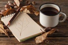 Dibuje a lápiz en el papel vacío del vintage, hojas de otoño en la tabla de madera Imágenes de archivo libres de regalías