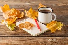 Dibuje a lápiz en el papel vacío del vintage, hojas de otoño en la tabla de madera Fotografía de archivo libre de regalías