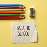 Dibuje a lápiz los creyones, los sacapuntas y el texto de nuevo a escuela Foto de archivo libre de regalías