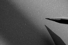 Dibuje a lápiz sostenerse a escribir en el papel en sombra Imagenes de archivo