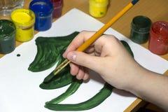Dibuje un árbol un abeto con el cepillo y pintura verde en una hoja blanca de Foto de archivo