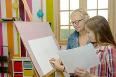 Dibujo adolescente joven de la muchacha con su profesor Imágenes de archivo libres de regalías