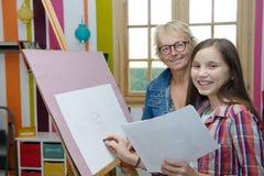 Dibujo adolescente joven de la muchacha con su profesor Fotos de archivo libres de regalías