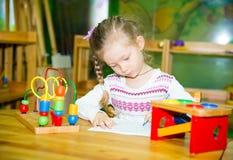 Dibujo adorable de la muchacha del niño con los lápices coloridos en sitio del cuarto de niños Niño en guardería en clase del pre Fotografía de archivo