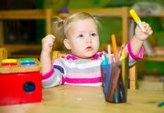 Dibujo adorable de la muchacha del niño con los lápices coloridos en sitio del cuarto de niños Niño en guardería en clase del pre Imagen de archivo libre de regalías