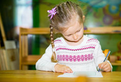 Dibujo adorable de la muchacha del niño con los lápices coloridos en sitio del cuarto de niños Niño en guardería en clase del pre Imagenes de archivo
