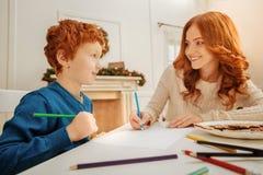 Dibujo alegre de la madre y del hijo con los lápices coloridos junto Foto de archivo