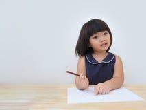 Dibujo asiático feliz de la muchacha del niño con el lápiz coloreado, niño que aprende y que juega en casa Imagenes de archivo