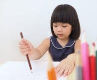 Dibujo asiático feliz de la muchacha del niño con el lápiz del color, niño que aprende y que juega en casa Imagenes de archivo