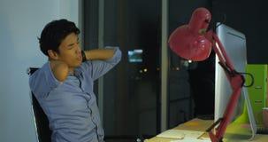 Dibujo asiático joven del artista en una pluma digital mientras que se sienta en su oficina Tarde en la noche almacen de video