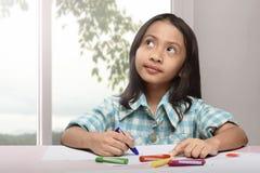 Dibujo asiático lindo del pequeño niño con el creyón colorido Imagen de archivo libre de regalías
