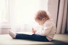 Dibujo caucásico de la niña con el lápiz en el papel, sentada en el sofá Fotografía de archivo libre de regalías