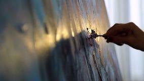 Dibujo con la esp?tula y las pinturas acr?licas La mano de un artista de la mujer, sosteniendo una esp?tula para dibujar y aplica almacen de metraje de vídeo