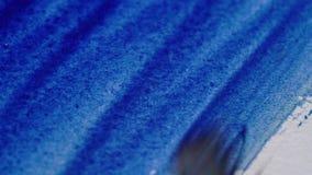 Dibujo con una brocha en el Libro Blanco con cierre azul de la acuarela para arriba metrajes