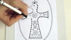Dibujo con una manija de la pluma del gel de un pájaro místico fabuloso El proceso de la creatividad