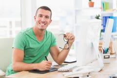 Dibujo creativo joven del hombre de negocios en la tableta gráfica imagen de archivo